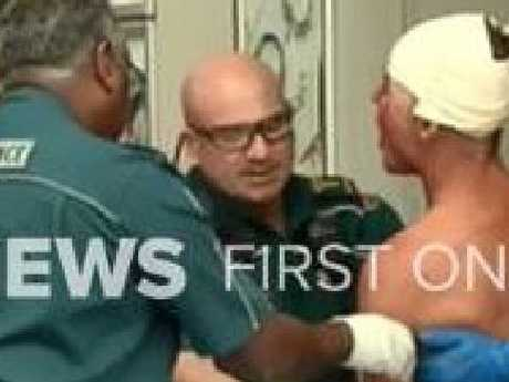 Ambulance officers treat a man at the scene of a brawl in Surfers Paradise.