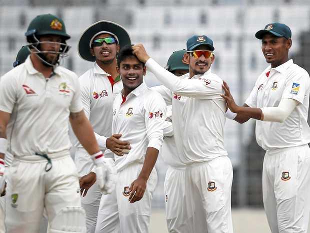 Teammates congratulate Bangladesh's Mehedi Hasan Miraz (centre) after the dismissal of Australia's Matthew Wade (left).