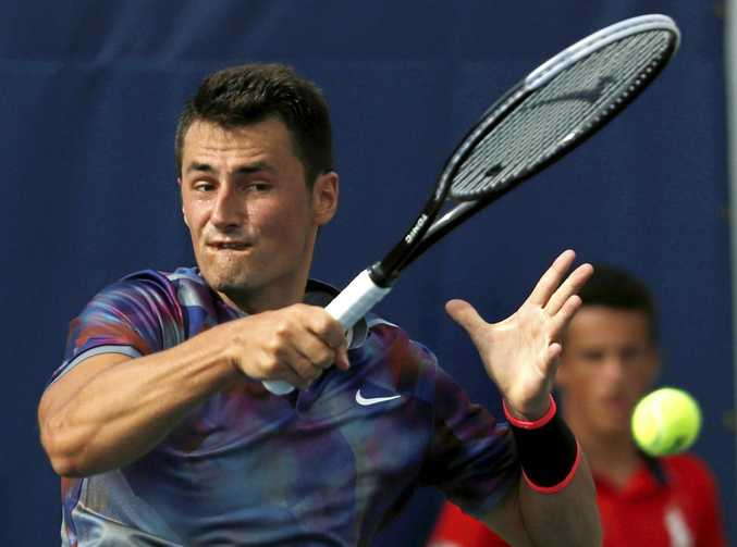 Bernard Tomic, of Australia, returns a shot from Gilles Muller, of Luxembourg, during the first round of the US Open.