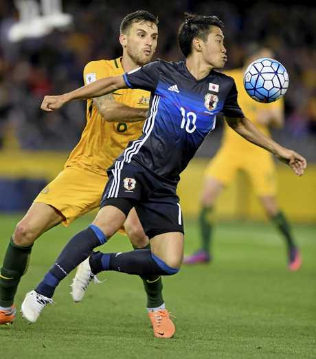 Japan's Shinji Kagawa and Australia's Matthew Spiranovic compete for the ball.