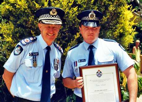 Senior Police Constable Stuart Allan (right)  awarded a Medal of Valour in 2002 by Police Commissioner Bob Atkinson.