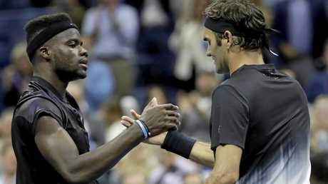 Roger Federer and Frances Tiafoe shake hands.