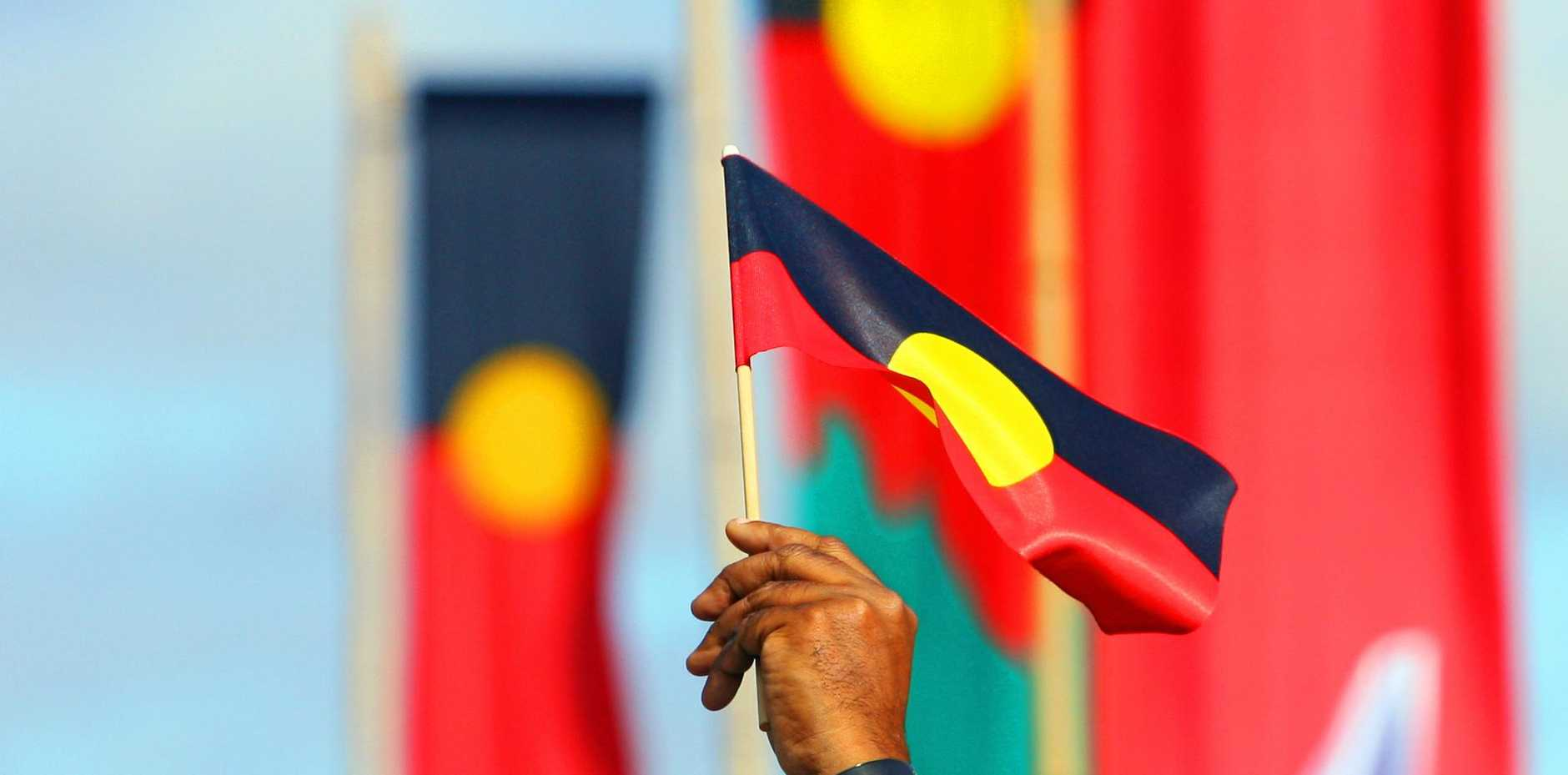Aboriginal flags fly during a NAIDOC Week march.