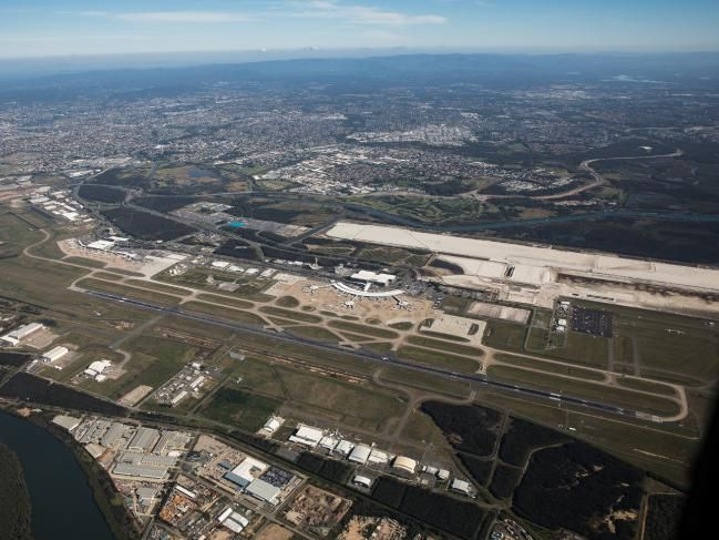 The new parallel runway (white strip behind terminal) being built at Brisbane Airport.