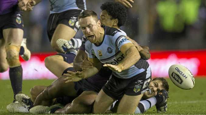 James Maloney of the Sharks spills the ball under the tackle of Ryley Jacks and Felise Kaufusi of the Storm in round 14.