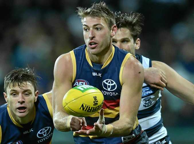 Daniel Talia of the Crows gets a handball away against the Cats.