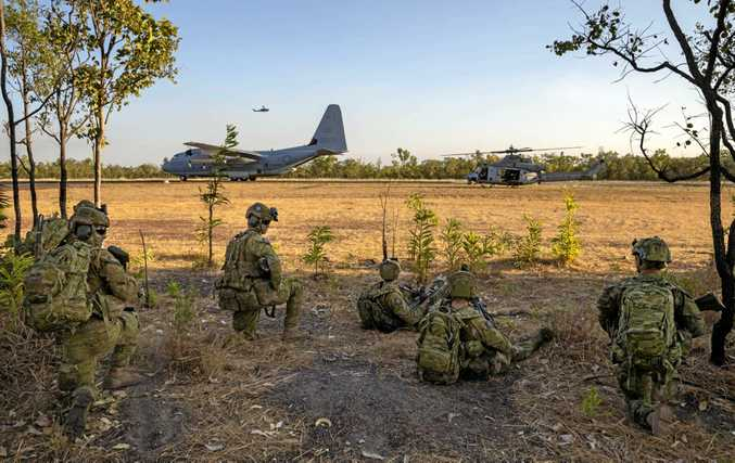Soldiers from the 5th Battalion, the Royal Australian Regiment watch on as United States Marine Corps C-130 Hercules, AH-1W Super Cobra and UH-1Y Venom aircraft prepare to depart the airstrip at Mount Bundey Training Area in the Northern Territory as part of Exercise Talisman Saber.