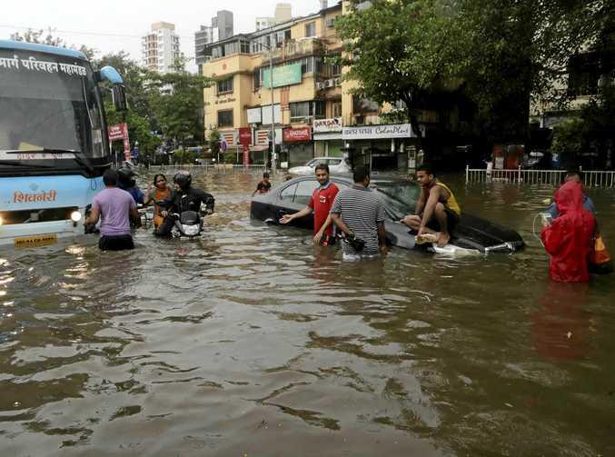 Commuters make their way through a waterlogged street following heavy rains in Mumbai, India.