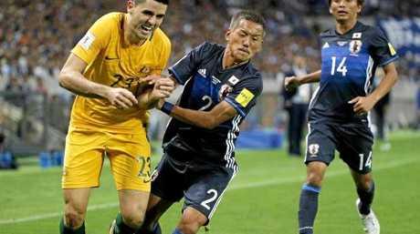 Tom Rogic is pushed off the ball by Yosuke Ideguchi. Photo:AP