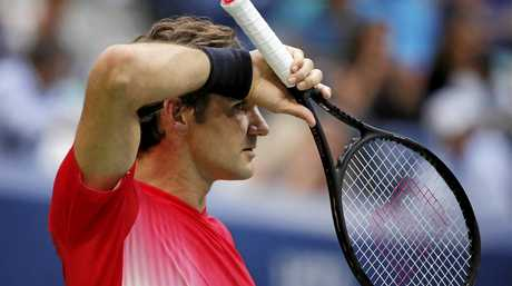 Roger Federer wipes sweat from his face between serves