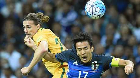 Jackson Irvine of Australia and Makoto Hasebe of Japan compete for the ball.