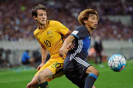 Takashi Inui of Japan competes for the ball with Robbie Kruse of Australia.