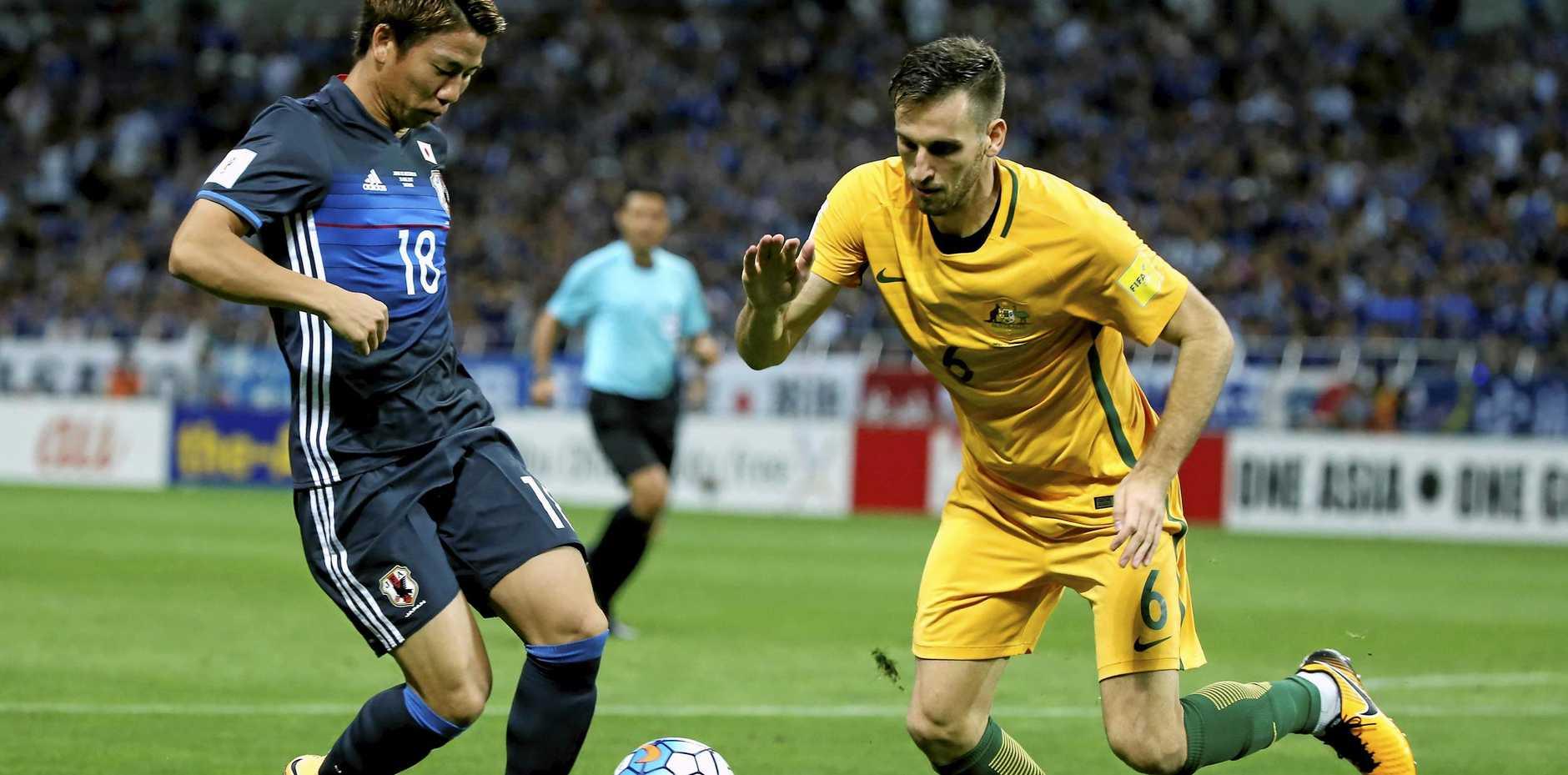 Australia's Matthew Spiranovic defends Japan's Takuma Asano during their World Cup qualifier in Saitama.