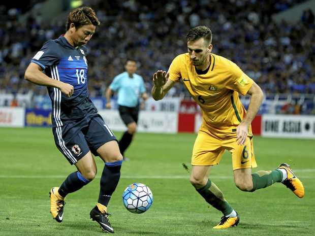 Australia's Matthew Spiranovic defends Japan's Takuma Asano during their World Cup qualifier in Saitama.