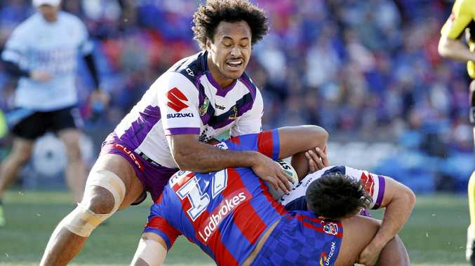 MINOR PREMIERS: Jacob Saifiti of the Knights is tackled by Felise Kaufusi of the Melbourne Storm.