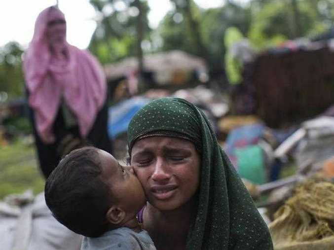 A Rohingya Muslim child places a kiss on his mother's cheek as they rest after having crossed over from Myanmar to the Bangladesh side of the border near Cox's Bazar's Teknaf area, Saturday, Sept. 2, 2017. Tens of thousands more people have crossed by boat and on foot into Bangladesh in the last 24 hours as they flee violence in western Myanmar, the UNHCR said Saturday.