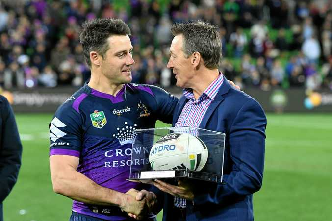 Cooper Cronk is presented with the match ball by coach Craig Bellamy after the round 26 match between the Storm and the Raiders at AAMI Park in Melbourne