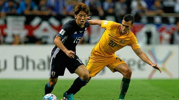 Yuya Osako of Japan controls the ball under pressure of Trent Sainsbury of Australia.