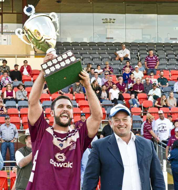 TROPHY TIME: Dalby captain Colin Green celebrates the TRL grand final win with Nick Barker from Hutchinson Builders.