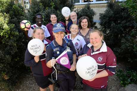 Students and staff from Ipswich State High School from left, Tarni Smith, Reech Mayer, Jessica Hernandez, resident police officer Senior Constable Storm Kolera, Haylee Breed, principal Simon Riley, chaplain Debbie Grey, and Shanai Malcolm are raising money for Bravehearts' White Balloon Day.