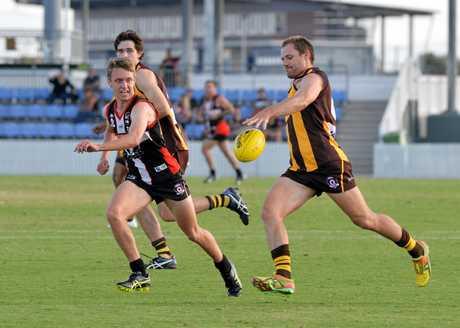 PRESSURE ON: Mackay City Hawks player Tim Bone   gets a kick away while being chased by North Mackay Saints player Luke Mason.