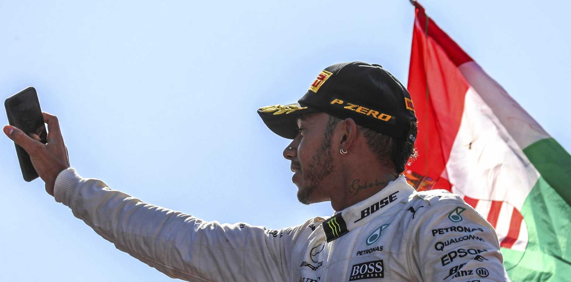 Lewis Hamilton takes a picture during celebrations on the podium after winning the Grand Prix of Italy
