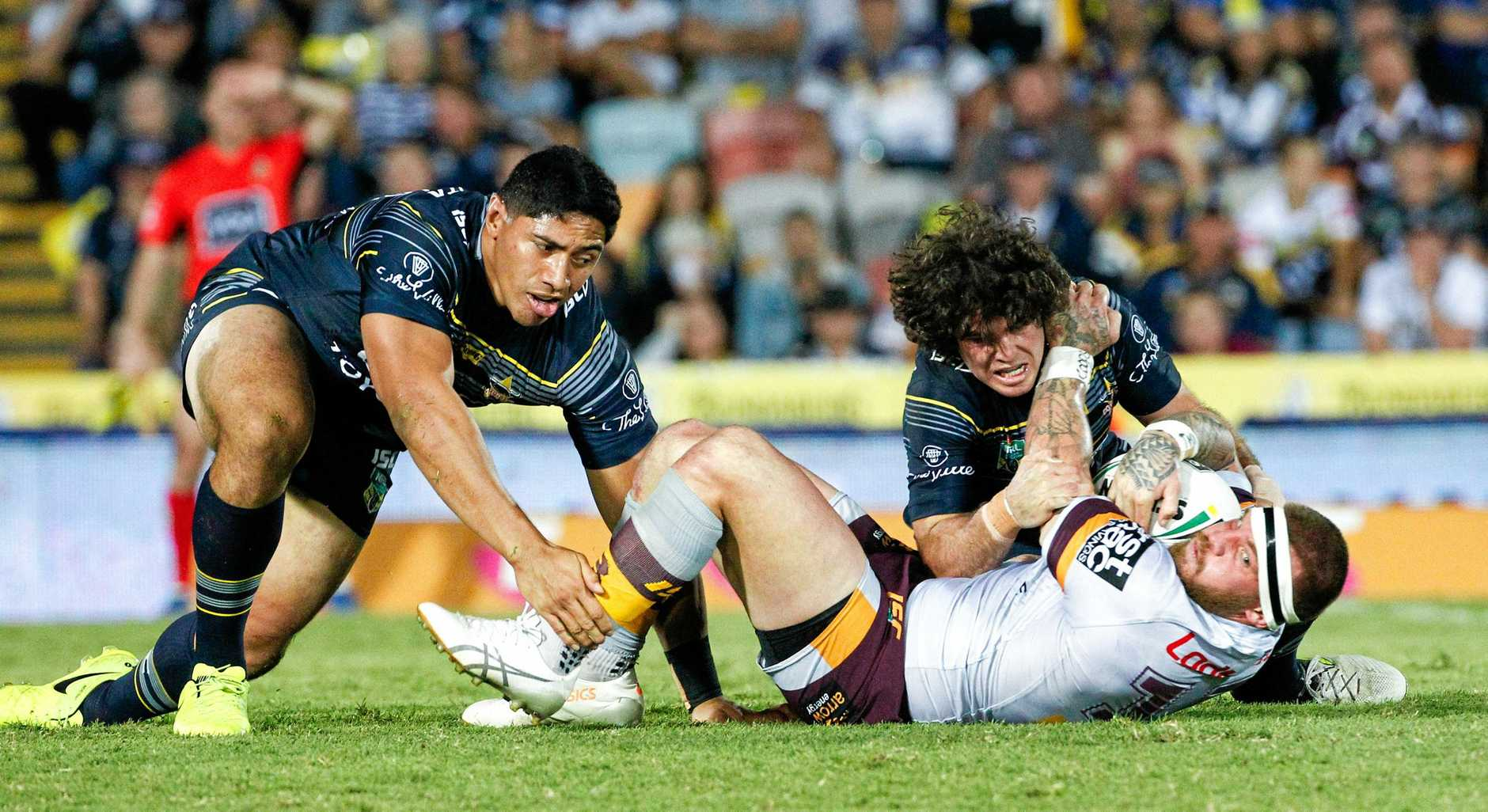 Josh McGuire of the Broncos is grounded by Cowboys Jason Taumalolo, left, and Jake Granville, right, during the Round 26 NRL match between the North Queensland Cowboys and the Brisbane Broncos at 1300SMILES Stadium in Townsville, Thursday, August 31, 2017. (AAP Image/Michael Chambers) NO ARCHIVING, EDITORIAL USE ONLY