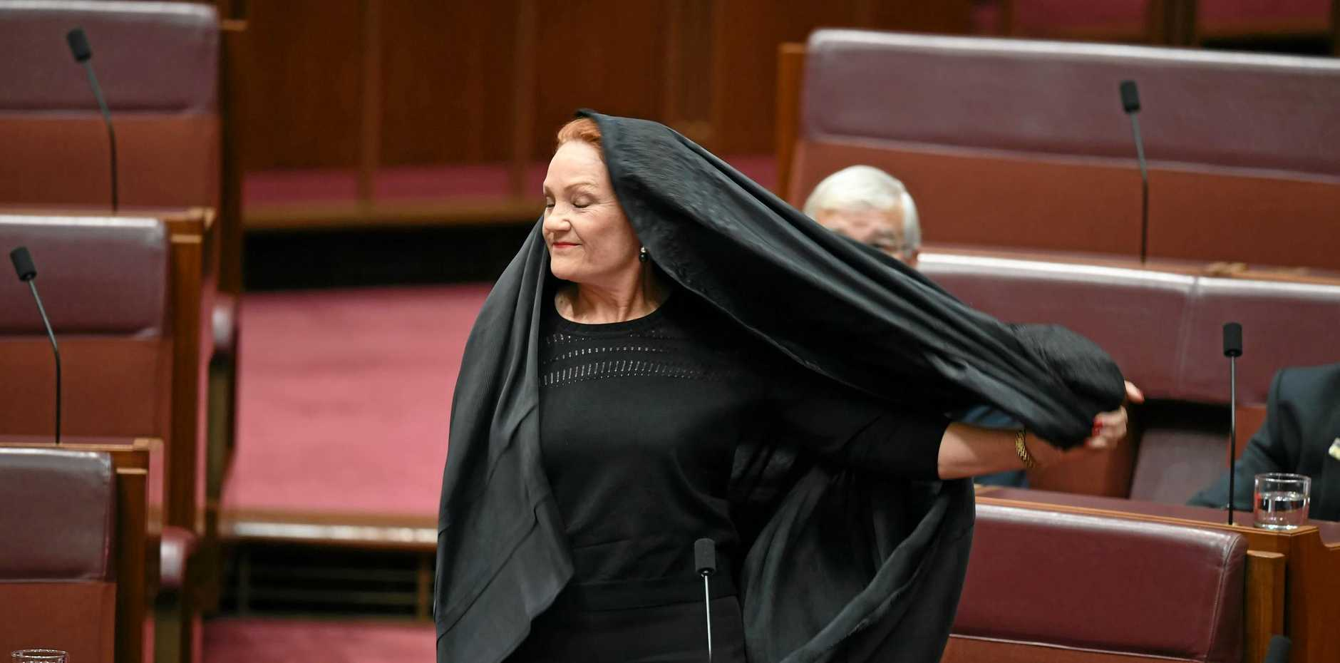 One Nation Senator Pauline Hanson takes off a burqa during Senate Question Time on August 17.