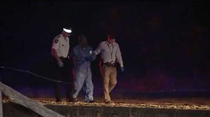 Bundaberg police lead a man away from the scene. 