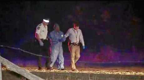 Bundaberg police lead a man away from the scene of a stabbing fataility last night.