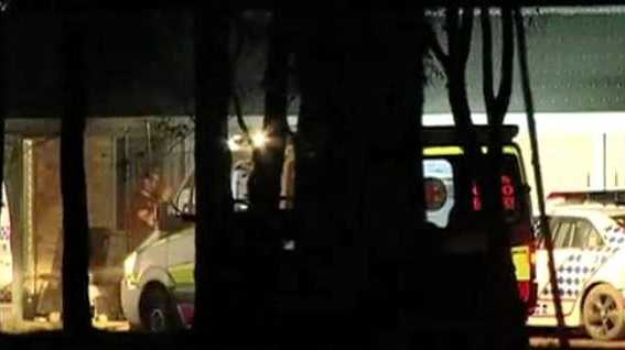 INVESTIGATION: Bundaberg police escort a man from the scene of a stabbing at Yandaran last night.