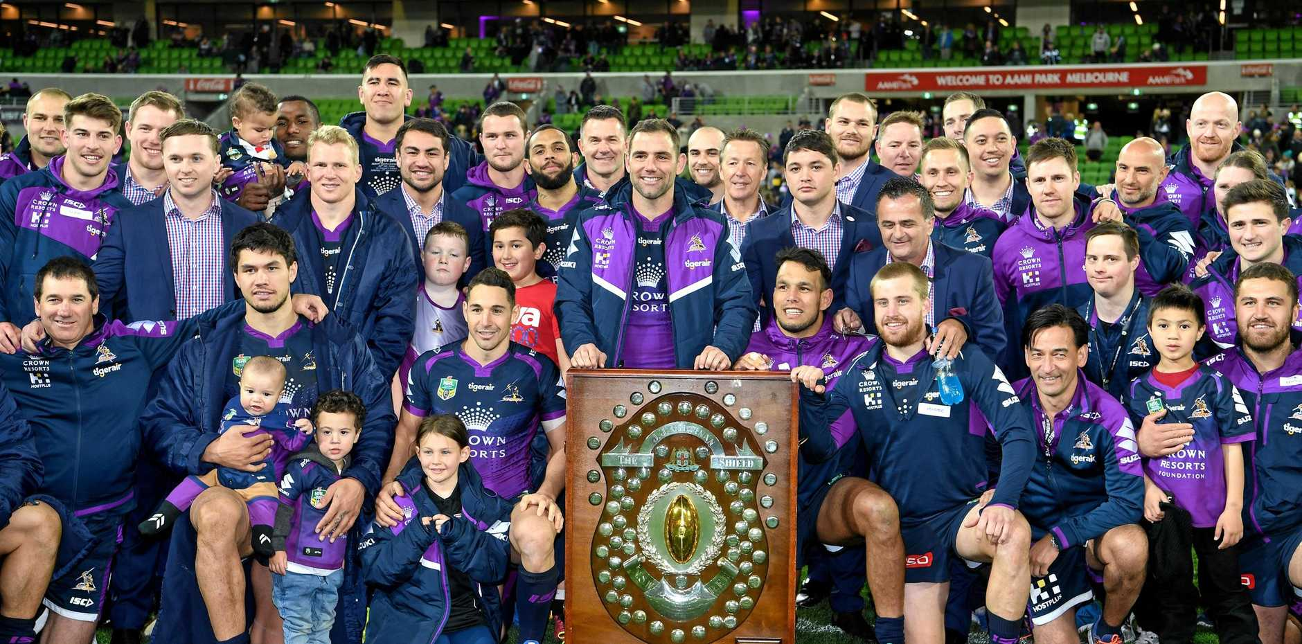 Storm players and officials pose with the J.J. Giltinan Shield, awarded to the NRL premiers, after the round 26 NRL match against the Canberra Raiders.