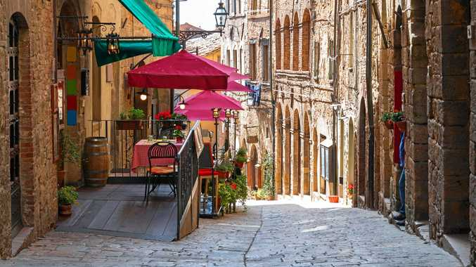 The charming narrow streets of Volterra in Tuscany and below right, the medieval palace Palazzo Dei Priori.