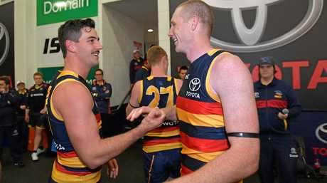 Taylor Walker and Sam Jacobs of the Crows celebrate in the changerooms.