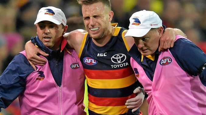 Brodie Smith of the Crows is carried off injured against the Giants.
