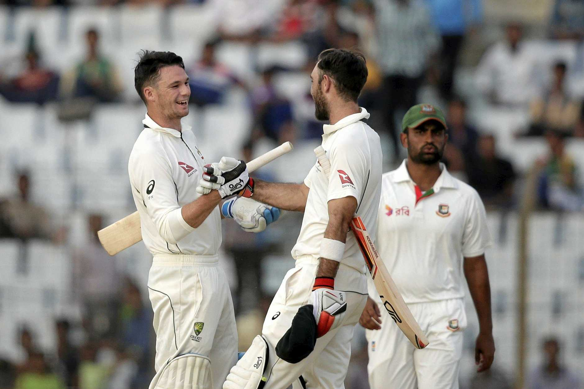Australia's Peter Handscomb, left, and Glenn Maxwell, center, celebrate their victory over Bangladesh, as Bangladesh's Tamim Iqbal watches during the fourth day of the second test cricket match in Chittagong, Bangladesh, Thursday, Sept. 7, 2017. (AP Photo/A.M. Ahad)