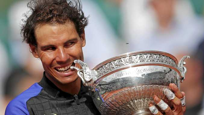 Spain's Rafael Nadal bites the trophy as he celebrates winning his tenth French Open title against Switzerland's Stan Wawrinka in three sets, 6-2, 6-3, 6-1, during their men's final match of the French Open tennis tournament at the Roland Garros stadium, in Paris, France, Sunday, June 11, 2017. (AP Photo/Christophe Ena)