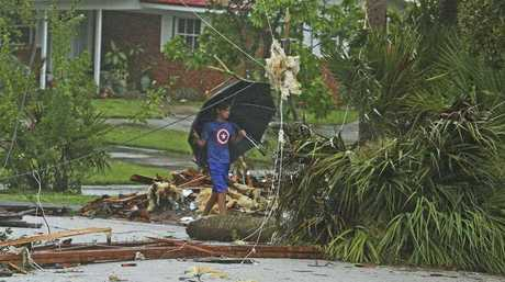 Aden Alcroix-Camper, 11, walks through debris from a second- story roof scattered over two block area after a possible tornado touched down at Palm Bay Point subdivision in Palm Bay Fla. (Red Huber/Orlando Sentinel via AP)