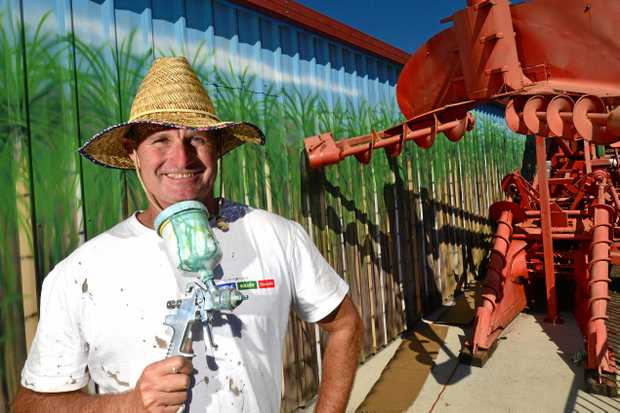 Owen Cavanagh works on his latest mural at the Nambour Historical Museum, which depicts the sugar cane industry.