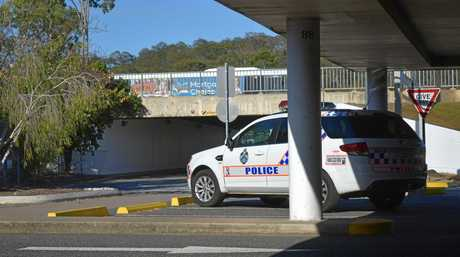 BASHING: Police inspected the scene of part of the attack underneath the overpass at Kmart Gladstone.