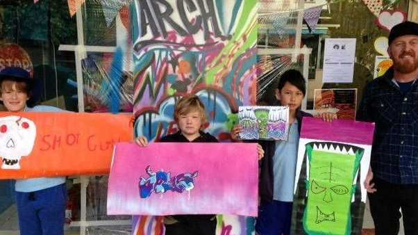 Finn, Levi and Padi create street art with artist Justin Livingstone at the ARCH community Arts Club on Carrington st in June.