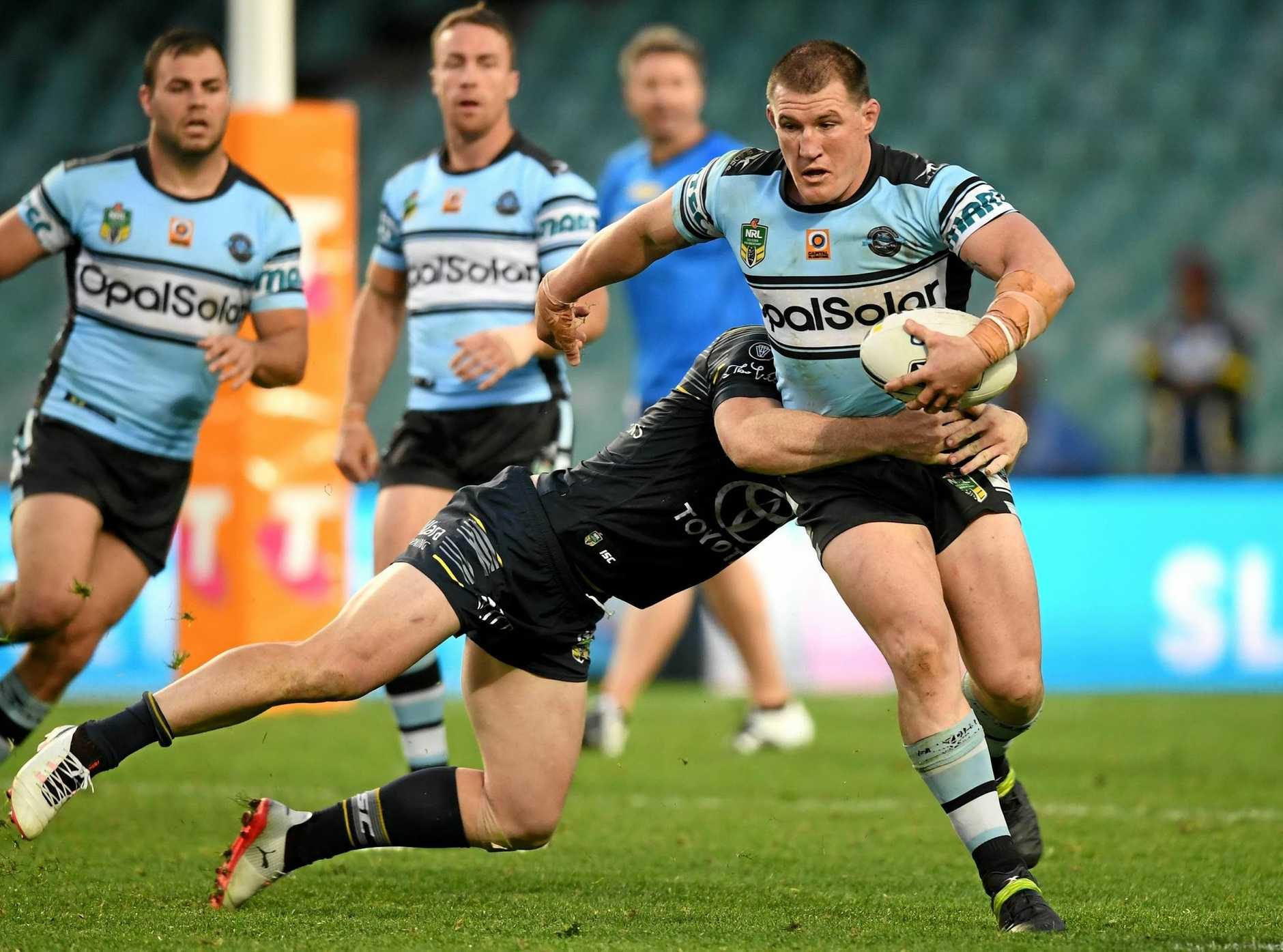 Paul Gallen of the Sharks is tackled by Michael Morgan of the Cowboys.