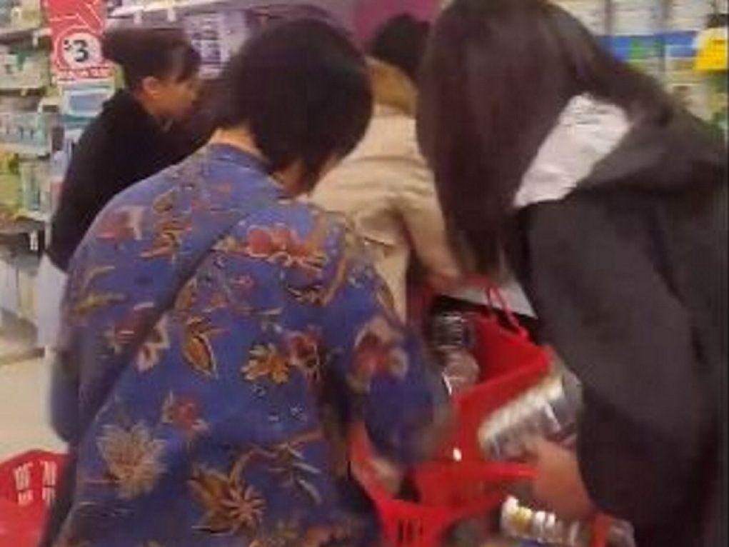 Women scramble to strip baby Coles shelves of baby formula.