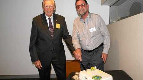 The club's longest-serving member Jim Bailey cuts the anniversary cake with newest member Ian McKenzie.