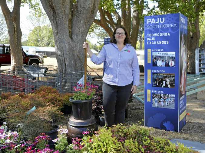 IT'S HERE: The Carnival of Flowers organiser Kate Scott sets up for the Ergon Energy Food and Wine Festival.