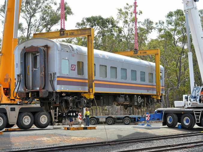HEAVY LIFT: Two cranes lift a carriage in place at the Central QLD University campus, Bundaberg.