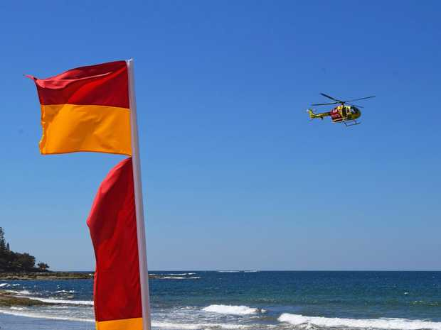 Surf Life Saving Queensland's Westpac Lifesaver Rescue Helicopter hovers over Kings Beach at Caloundra.
