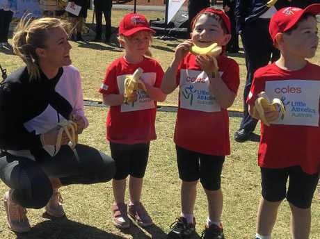 Sally Pearson hands out bananas to junior athletes during the announcement of a new deal between Athletics Australia, Little Athletics and supermarket chain Coles.