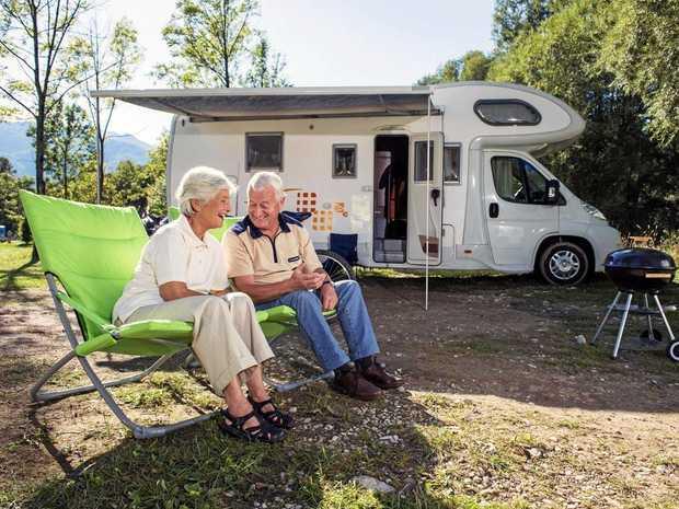 A senior couple having fun camping with camper van.