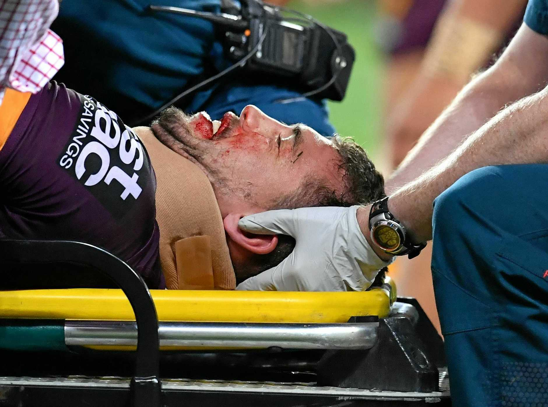Corey Oates of the Broncos is treated by medical staff after being injured.